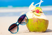 Picture of fresh cocnut cocktail and red sunglasses on tropical beach — Stock Photo