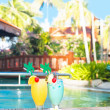 Two glasses of cocktails and flower near pool. party — Stock Photo #44540373