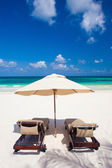 Two beach chairs and umbrella on white sand beach. Holidays — Stock Photo