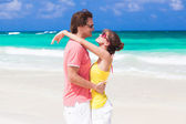 Half face view of romantic couple hugging on tropical beach — Stock Photo