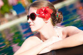 Beautiful young woman in sunglasses with flower in hair smiling in luxury pool — Zdjęcie stockowe