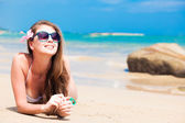 Long haired girl in bikini and sunglasses on tropical beach — Stok fotoğraf