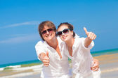 Front view of happy young couple on beach smiling and hugging. Thumbs up — Stock Photo