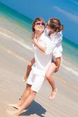 Couple in white clothes piggybacking cheerful on beach — Stockfoto