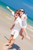 Par åka snålskjuts glada på stranden — Stockfoto