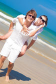 Photo of Happy couple in sunglasses on holiday piggybacking cheerful on beach — Stock Photo