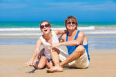 Front view happy young couple in bright clothes in sunglasses sitting on beach — Foto de Stock