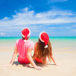 Young couple in santa hats laughing on tropical beach. new year — Stock Photo #46627943