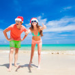 Young couple in santa hats laughing on tropical beach. new year — Stock Photo #46627949
