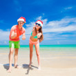 Young couple in santa hats laughing on tropical beach. new year — Stock Photo #46627953