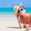 Front view of long haired young woman in bikini with a straw hat lying on tropical beach — Stock Photo #46627965