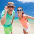Portrait of happy young couple in bright clothes and sunglasses having fun on tropical beach — Stock Photo #46628037