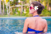 Half face portrait of young attractive woman relaxing at tropical pool — Stock Photo