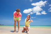 Portrait of happy young couple in bright clothes and sunglasses having fun on tropical beach — Stock Photo