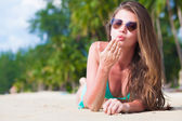 Front view of long haired young woman in bikini lying on tropical beach — Stock Photo