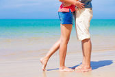 Legs of young kissing couple on tropical turquoise Thailand beach — Stock Photo
