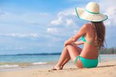 Long haired girl in bikini and straw hat on tropical beach — Stock Photo