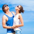 Young couple hugging and looking at the sun at tropical beach — Stock Photo #47406513