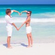 Young happy couple making heart shape on tropical beach. honeymoon — Stock Photo #47406761