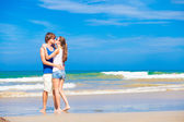 Happy young couple kissing at tropical beach — Stock Photo