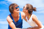 Portrait of happy young couple in sunglasses having fun at tropical beach — Stok fotoğraf