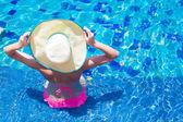 Jovem mulher com chapéu grande e biquíni rosa relaxante na piscina — Fotografia Stock