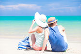 Happy young couple in straw hats sitting at tropical beach with beach bag — Stok fotoğraf