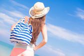 Back view of a woman with stripy bag and straw hat at tropical beach — Stok fotoğraf