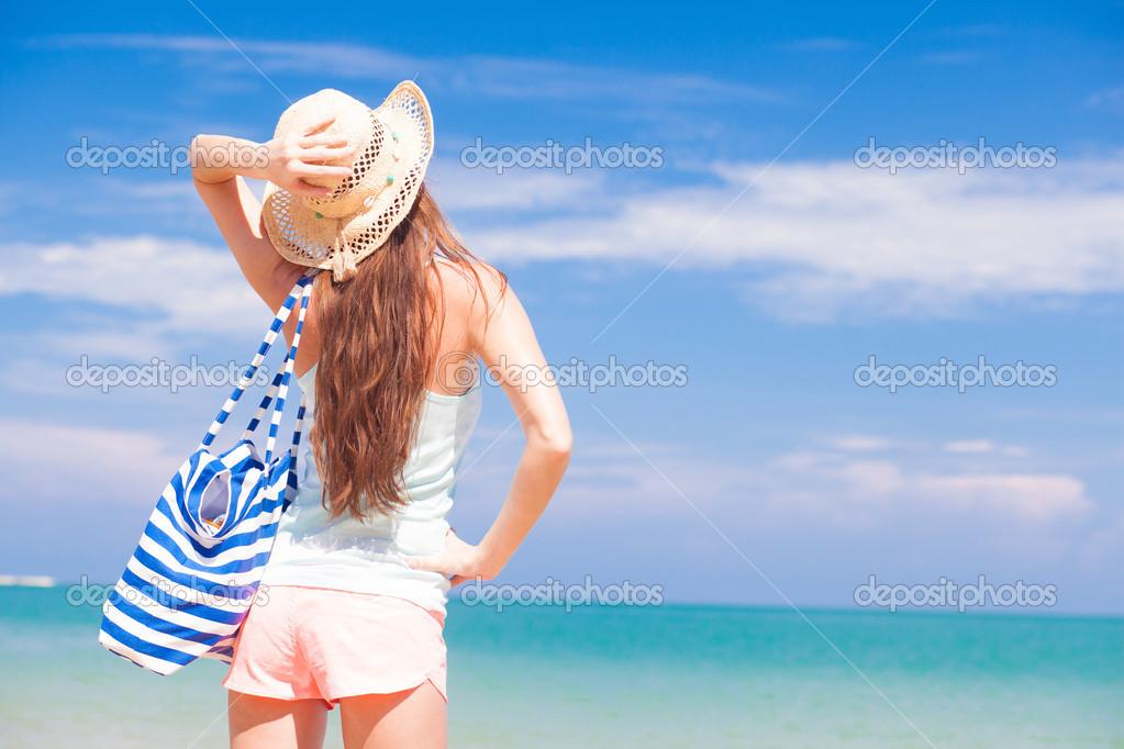 Vista di una donna con la borsa a righe e cappello di for Disegni di casa sulla spiaggia tropicale