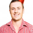 Merry young man in a party hat - Photo