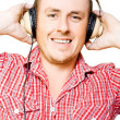 Stock Photo: Young mlistening to music through earphones