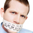 Isolated man with tape measure around mouth - Stock Photo