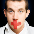 Silent handsome doctor with cross bandage on face - Stock Photo