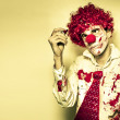 Royalty-Free Stock Photo: Horror Clown Writing Halloween Message In Blood