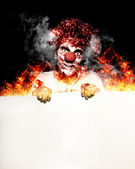 Scary Clown Holding Blank Board In Flames And Fire — Stock Photo