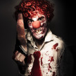 Foto de Stock  : Angry Horror Clown Holding Butcher Saw In Darkness
