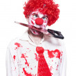 Spooky Clown Holding Bloody Saw In Mouth On White - 图库照片