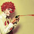 Stock Photo: Creepy Manic Clown Shooting Blood From Cap Gun