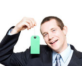 Happy store sales man with blank price tag — Stock Photo