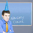 Businessman In Trouble Sitting In Naughty Corner - Stock Photo