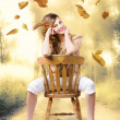 Beautiful woman sitting in autumn field - Stockfoto