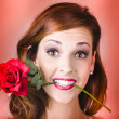 Woman gripping red rose between her teeth - Stockfoto