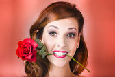 Woman gripping red rose between her teeth — Stock Photo
