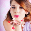 Portrait of a beautiful woman blowing heart kiss — Stock Photo