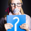 Foto Stock: Cautious WomHolding Book Of Education Questions