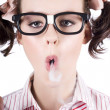 Nerd girl blowing smoke rings from cigarette - Stockfoto