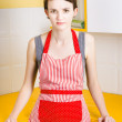 Young house wife on yellow kitchen background - Stock Photo