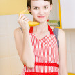 Stock Photo: Cute girl talking on fruit phone in kitchen