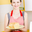 Smiling woman holding fresh loaf of homemade bread — Stock Photo
