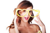 Funny woman with heart shape sunglasses — Stock Photo